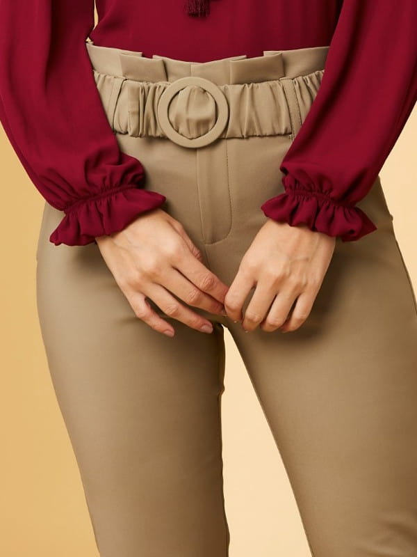Modelagem Clochard: em alta o ano todo: modelo com uma calça clohcard bege e camisa vinho.