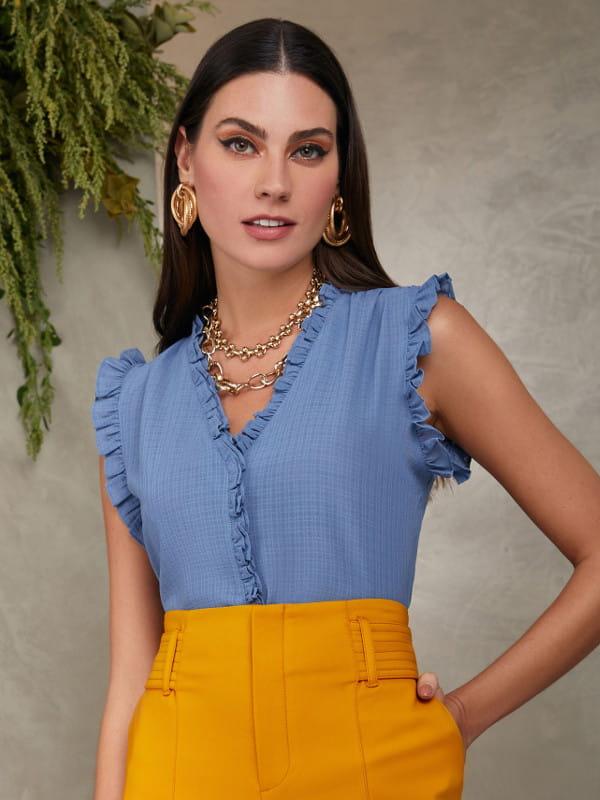 Modelos de blusas femininas: modelo vestindo uma blusa de crepe chiffon com babadinhos na cor azul.