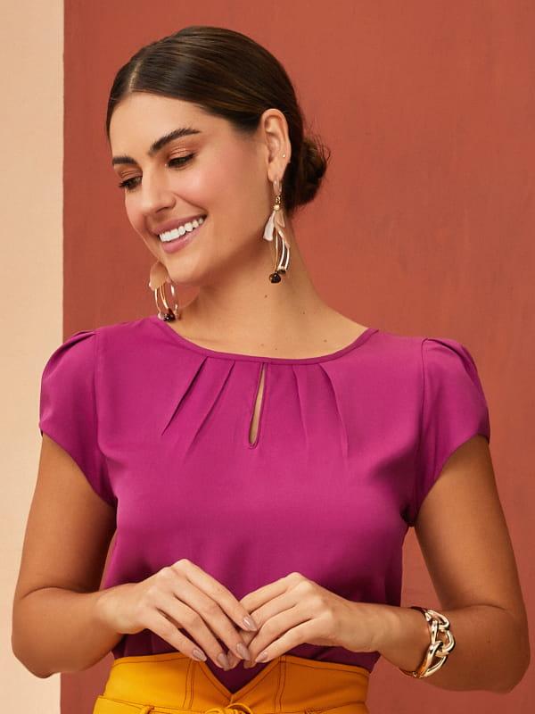 Modelos de blusas femininas: modelo com uma blusa de crepe detalhe gota cor fucsia.