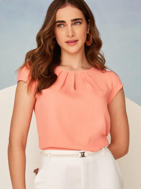 Modelo vestindo uma blusa de crepe com detalhe em gota na cor laranja.
