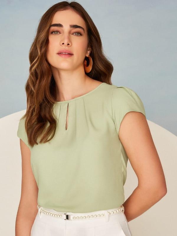 Modelo vestindo uma blusa de crepe com detalhe em gota na cor verde.