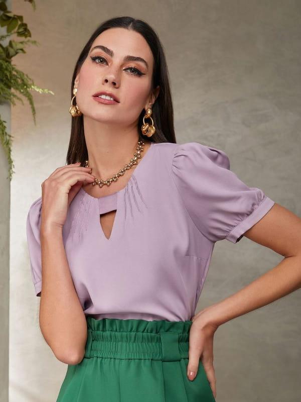 Modelo vestindo uma blusa de crepe lilás com decote triângulo.