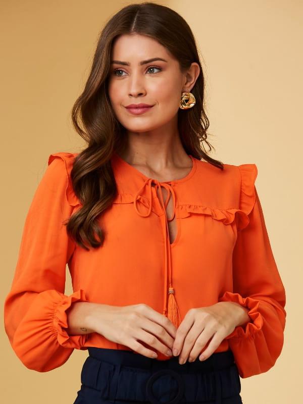 Modelos de blusas femininas: modelo com uma blusa de blusa de crepe manga longa amarração e tassel.