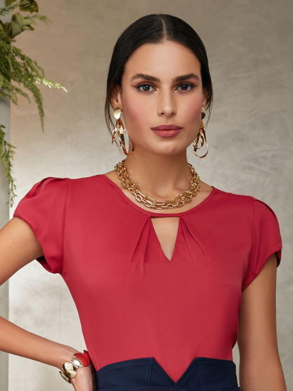 Modelos de blusas femininas: mulher vestindo uma blusa de crepe vermelha com decote triângulo.