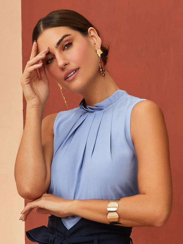 Modelos de blusas femininas: modelo vestindo uma regata de crepe com pregas azul clara.