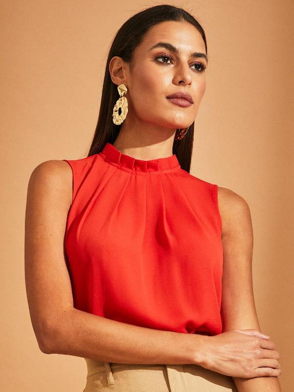 O poder das cores vibrantes: modelo vestindo uma blusa de crepe básica com pregas laranja.