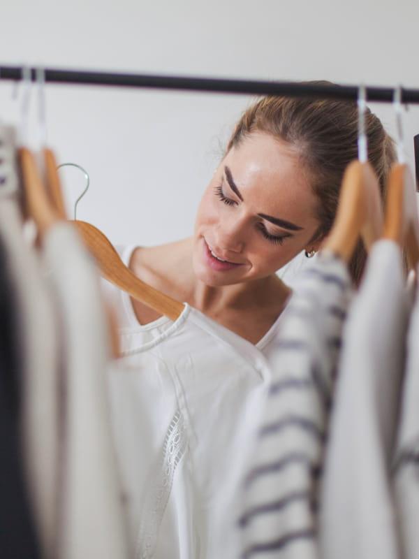 Peças fundamentais no guarda-roupa feminino: mulher escolhendo modelos atrás de uma arara de roupas.