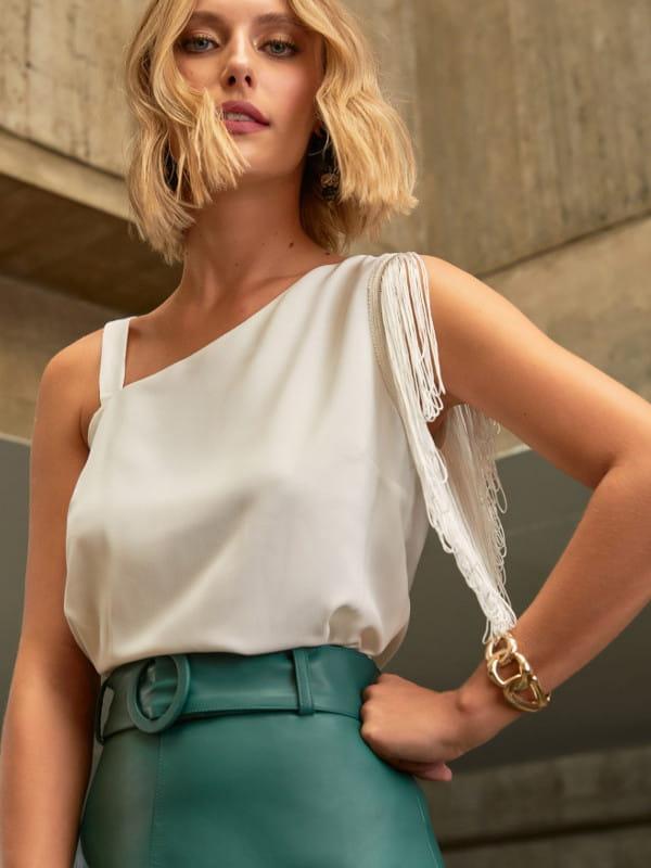 Qual decote usar para favorecer meu corpo: modelo vestindo uma blusa com decote assimétrico.