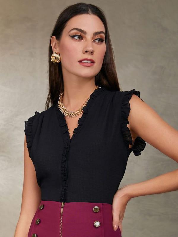 Que cor combina com preto: modelo vestindo uma blusa de crepe chiffon com babadinhos preta.