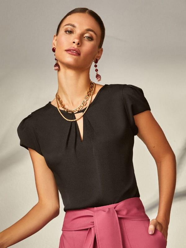 Que cor combina com preto: modelo vestindo uma blusa de crepe decote triângulo e pregas.