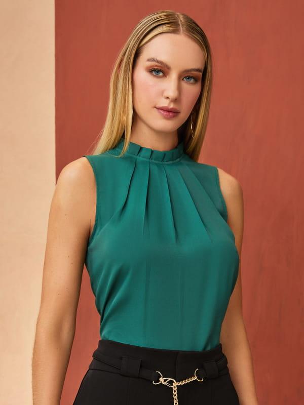 Que cor combina com preto: modelo vestindo uma blusa de crepe básica com pregas verde.
