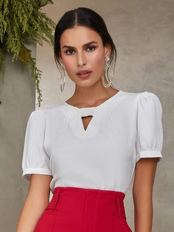 Roupa social feminina: modelo vestindo uma blusa de crepe branca com decote triângulo e mangas bufantes.