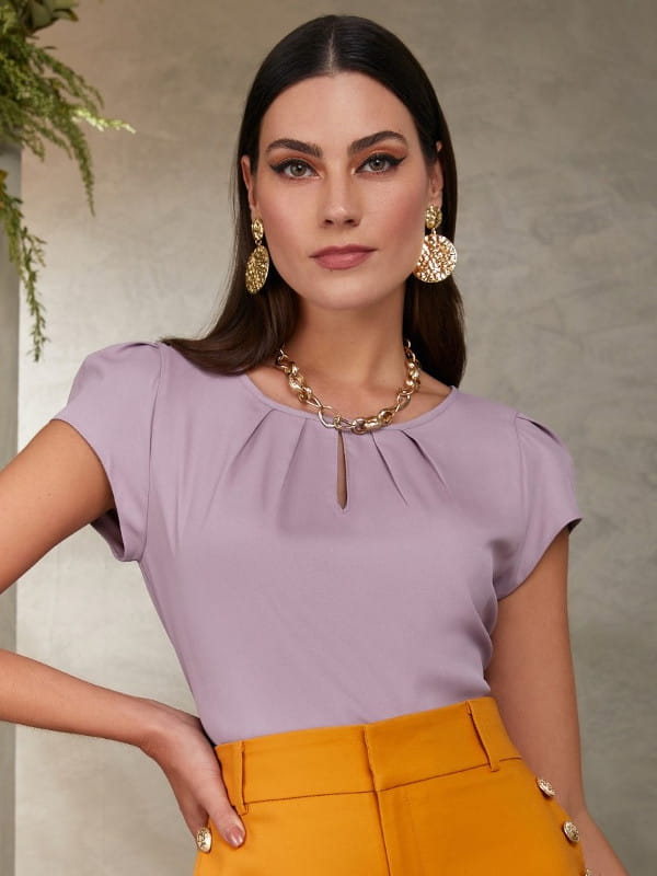 Roupa social feminina: modelo vestindo uma blusa de crepe lilás com decote redonda formato de uma gota.