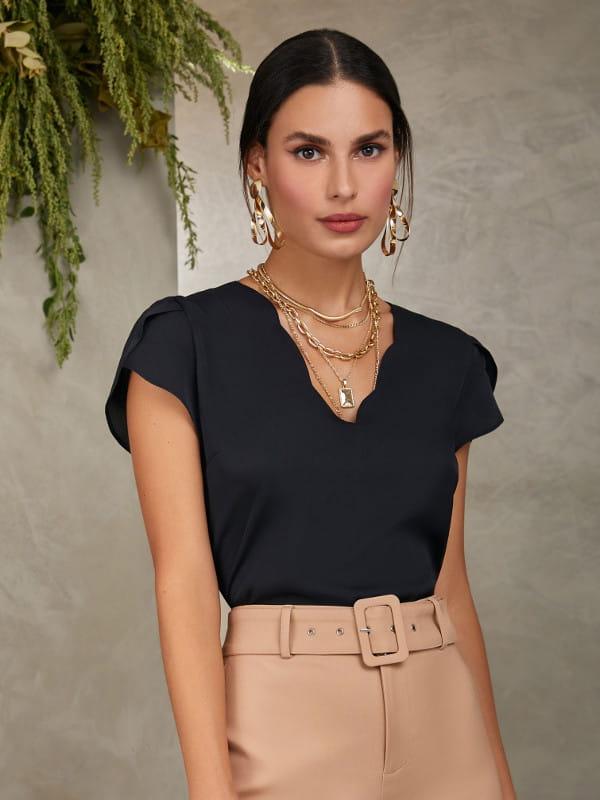 Roupa social feminina: modelo vestindo uma blusa de crepe preta com decote V em formato de nuvem.