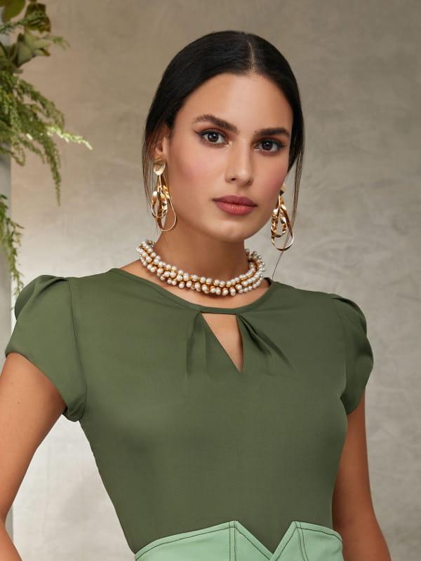 Roupa social feminina: modelo vestindo uma blusa de crepe verde com decote triângulo.