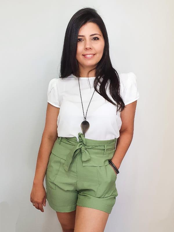 Roupas para Ano Novo: modelo vestindo bermuda de viscose verde com blusa de crepe branca.