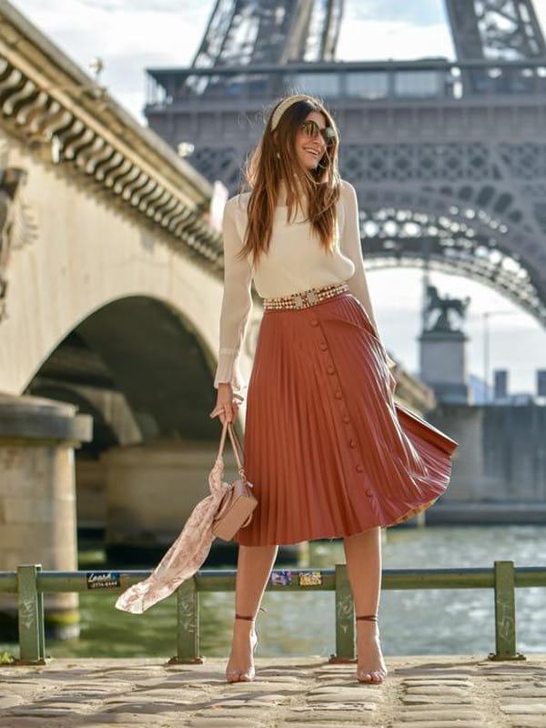 Saia midi plissada: modelo vestindo uma saia midi de couro marrom.
