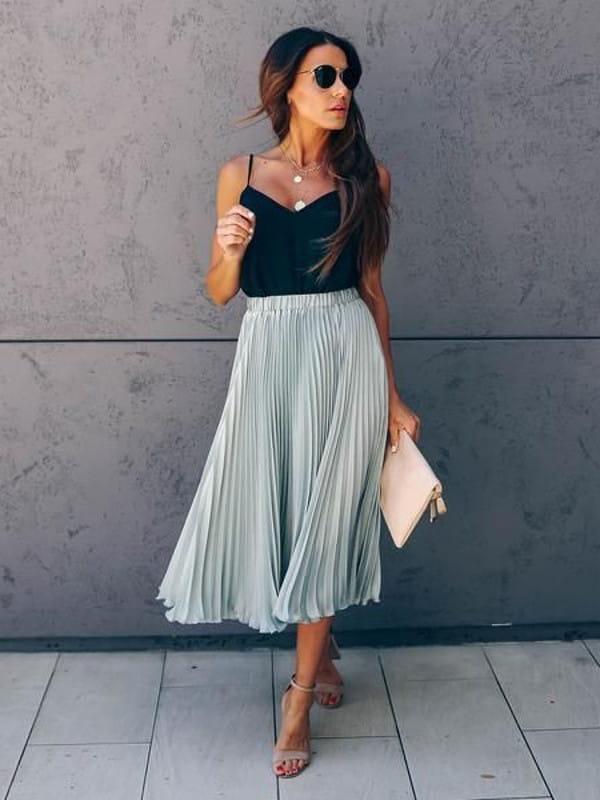 Saia midi plissada: modelo vestindo uma saia midi e regata.