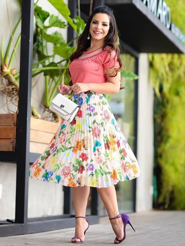 Saia midi plissada: modelo vestindo uma saia midi estampada.