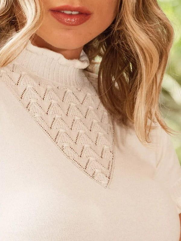 Tendência Tricot Inverno 2021: modelo com uma blusa de tricot com links e babados mostrando detalhes.