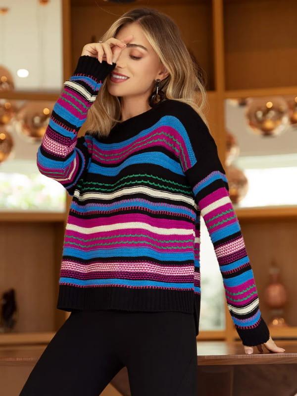 Tendência Tricot Inverno 2021: modelo vestindo uma blusa de tricot com listras variadas coloridas.