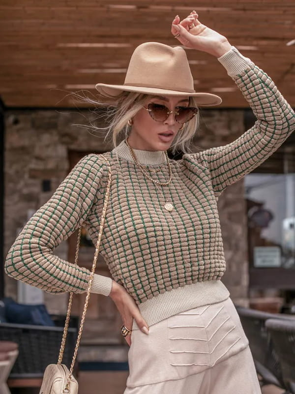 Tendência Tricot Inverno 2021: modelo vestindo uma blusa de tricot manga longa dropper bege.