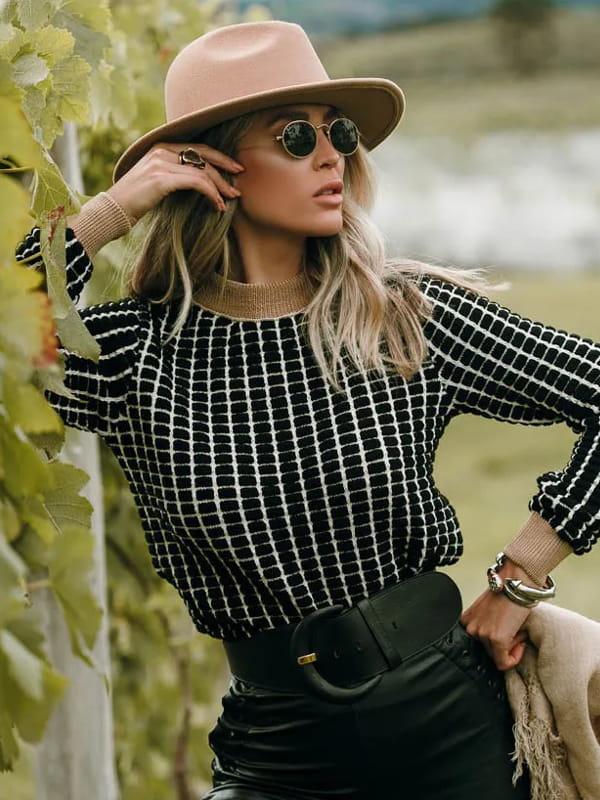Tendência Tricot Inverno 2021: modelo vestindo uma blusa de tricot manga longa dropper preta.