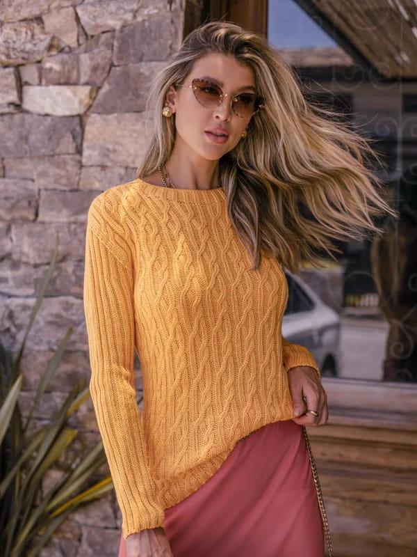 Tendência Tricot Inverno 2021: modelo vestindo uma blusa de tricot com com trança e manga canelada.