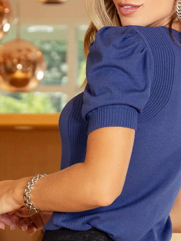 Tendência Tricot Inverno 2021: modelo vestindo uma blusa azul de tricot com mangas bufantes mostrando as costas.