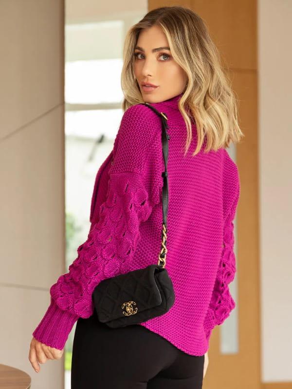 Tendência Tricot Inverno 2021: modelo com um casaco de tricot e mangas gomos mostrando as costas.