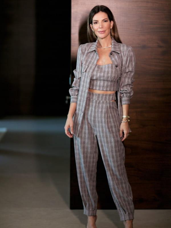 Tendências de calças femininas para 2021: modelo usando uma calça alfaiataria xadrez com blusinha no mesmo tom.