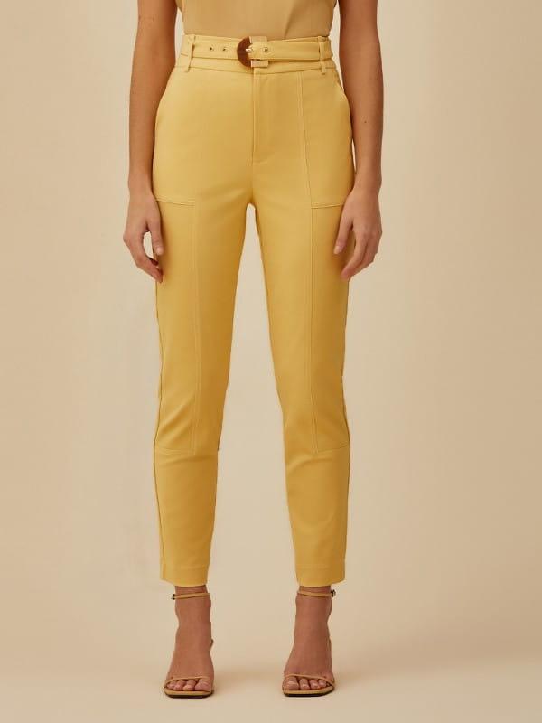 Tendências de calças femininas para 2021: modelo usando uma calça skinny mostarda.