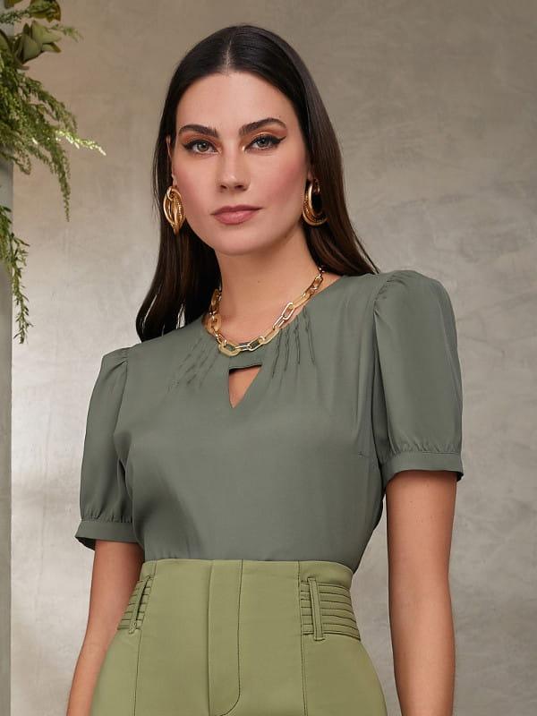 Tendências de cores para 2021: modelo vestindo uma blusa de crepe verde com elástico no decote.