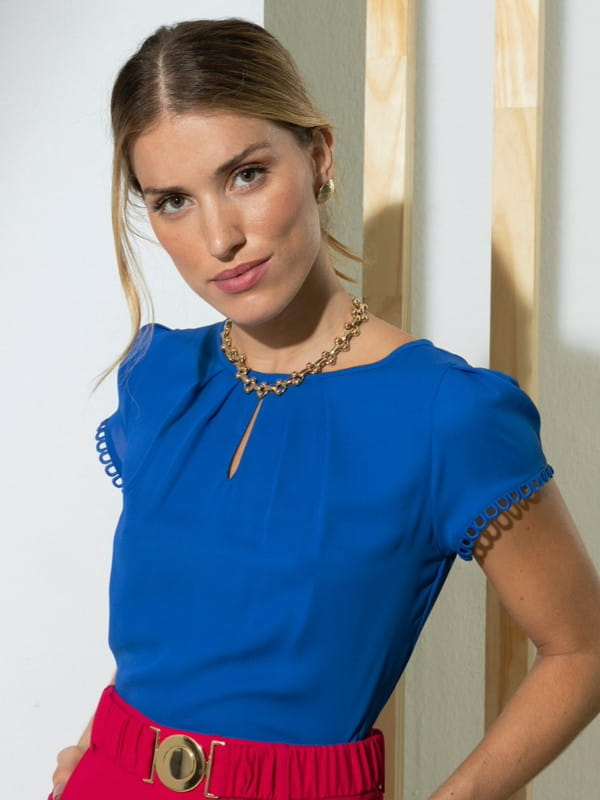 Tendências de cores para 2021: modelo vestindo uma blusa de crepe azul com renda nas mangas.
