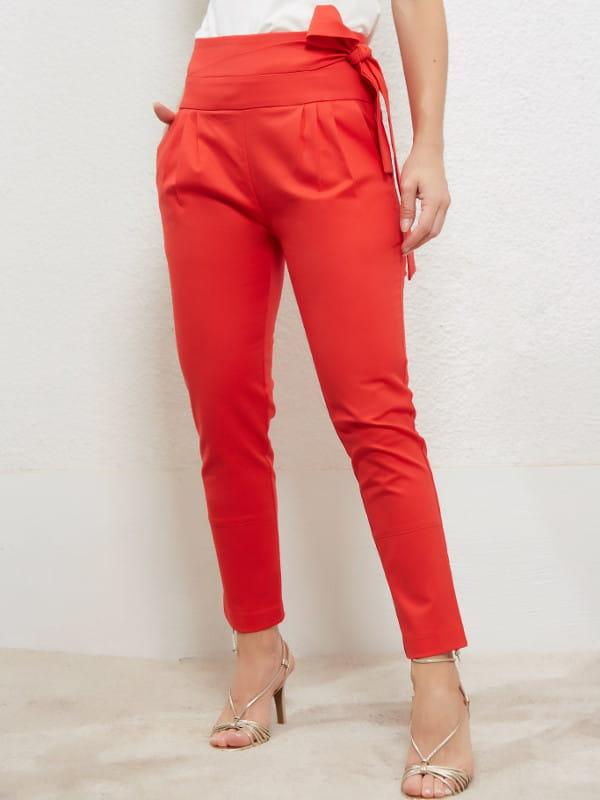 Tendências de looks com amarrações: modelo usando uma calça carrot com amarração na cintura.
