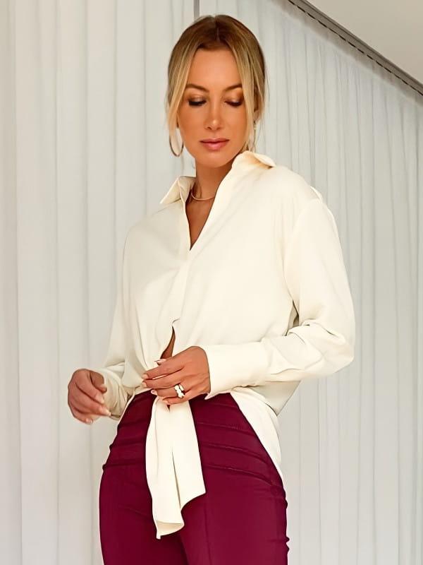 Tendências de looks com amarrações: modelo usando uma camisa off white amarrada na cintura.
