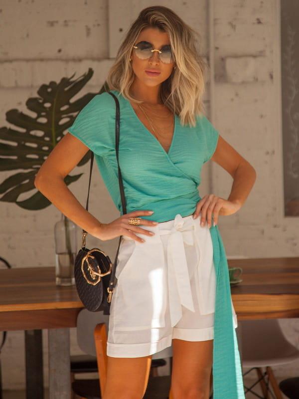 Tendências de looks com amarrações: modelo usando uma blusa verde com amarração e shorts branco.