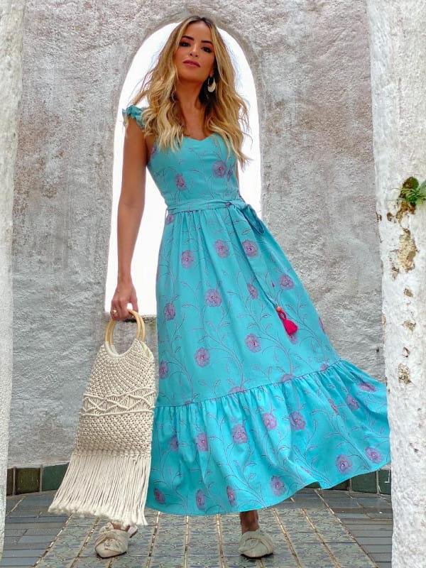 Tendências de looks com amarrações: modelo usando um vestido azul com amarração na cintura.