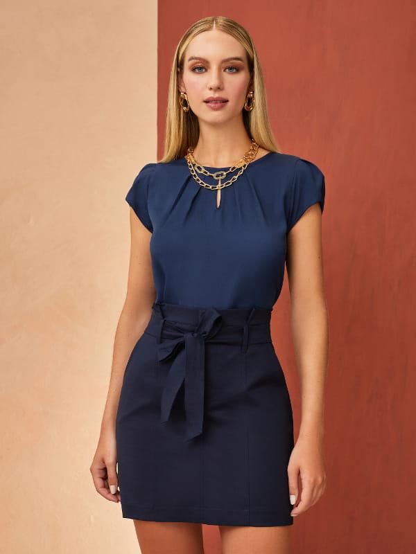 Tendências primavera verão 2021: modelo vestindo uma blusa azul marinho com saia na mesma cor.