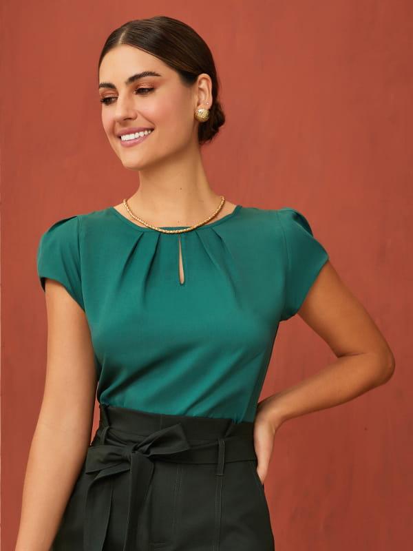 Tendências primavera verão 2021: modelo vestindo uma blusa de crepe gota na cor verde.