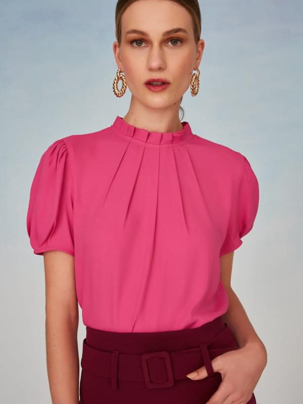 Tendências primavera verão 2022: modelo vestindo uma blusa com pregas na gola.