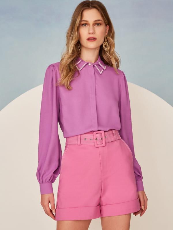 Tendências primavera verão 2022: modelo vestindo uma camisa com pérolas na gola.