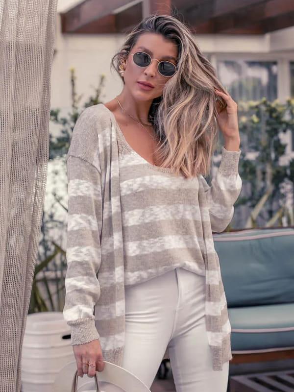 Blusa de tricot feminina: modelo vestindo um casaco de tricot e regata listrada.