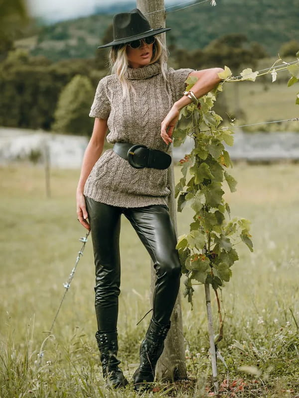 Colete de tricot feminino: modelo sentada vestindo um colete de tricot marrom com calça skinny preta.
