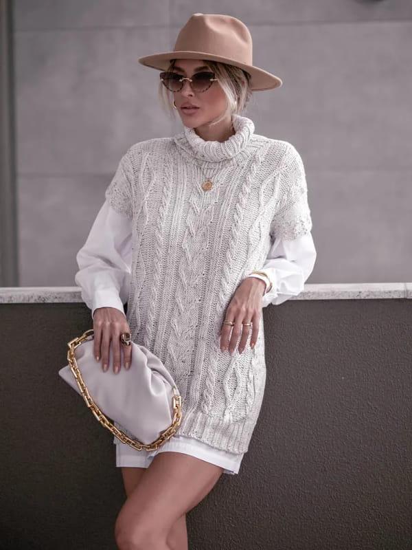 Colete de tricot feminino: modelo sentada vestindo um colete de tricot longo na cor areia.
