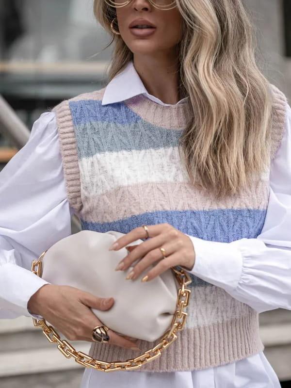 Colete de tricot feminino: modelo sentada vestindo um colete de tricot listrado com camisa branca.