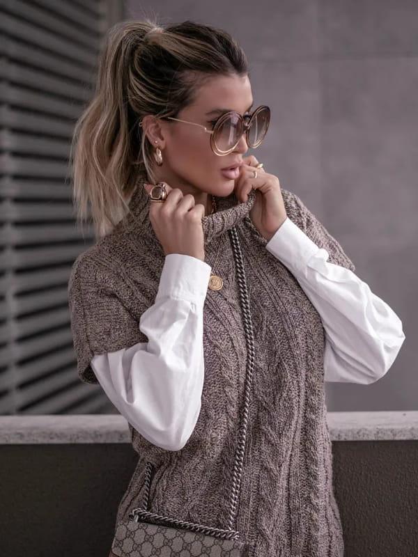 Colete de tricot feminino: modelo vestindo um colete de tricot feminino marrom com gola alta.