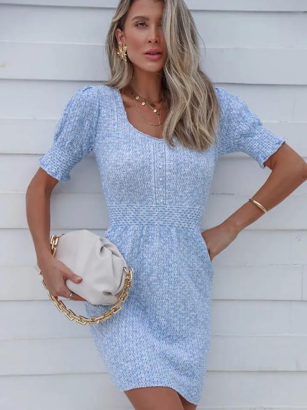 Vestido de tricot: modelo mostrando detalhes de um vestido de tricot curto azul com pérolas.