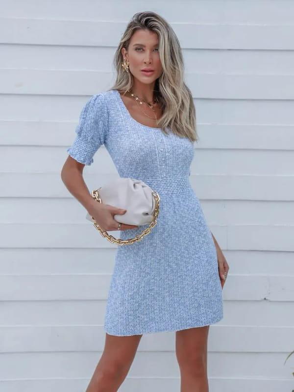 Vestido de tricot: modelo vestindo um vestido de tricot curto azul com pérolas.