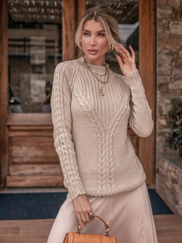 Vera Tricot: Onde comprar no varejo: modelo usando uma blusa de tricot com trança ponto arroz.